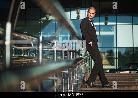 handsome elegant groom leaning on metal handrails holding hands in pockets of elegant suit - Stock Photo