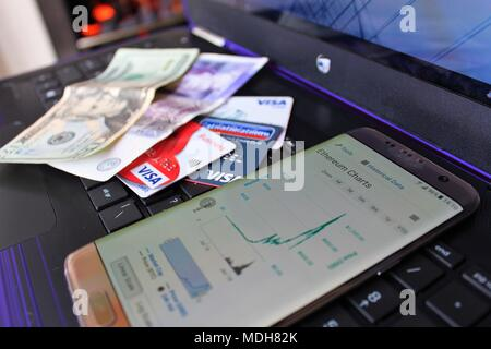 Ethereum 'Cryptocurrency' Market Cap chart showing a price crash, on a Smartphone on top of a laptop, with older/current currencies in background. - Stock Photo