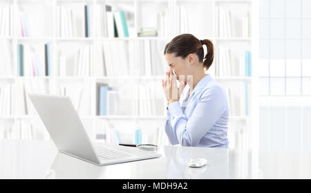 Business woman or a clerk working at her office desk with computer she is sick and sneezes - Stock Photo
