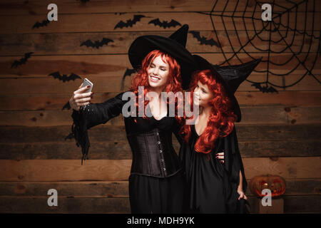 Halloween Concept - Beautiful caucasian mother and her daughter with long red hair in witch costumes taking a selfie with smartphone  ready for celebrating Halloween. - Stock Photo