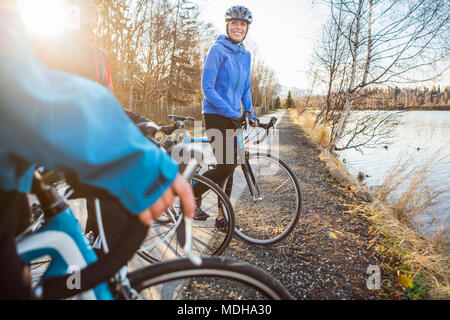 Three young women on their bicycles on a trail at sunrise; Anchorage, Alaska, United States of America - Stock Photo