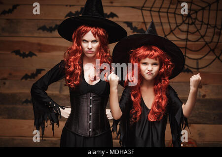 Halloween Concept - Beautiful caucasian mother and her daughter with long red hair in witch costumes witch cheerful fighting facial expression. - Stock Photo