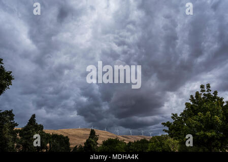 Dark clouds loom over Klickitat County with wind turbines on the hills; Maryhill, Washington, United States of America - Stock Photo