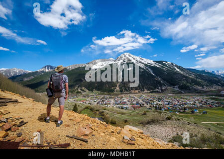 A senior man hiking with a view of Kendall Mountain in the distance; Silverton, Colorado, United States of America - Stock Photo