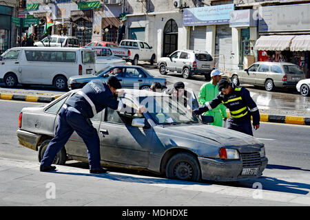 Amman police helping a motorist with car trouble. A move to clear the streets ahead of a parade in Amman, Jordan. - Stock Photo