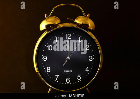 Old retro alarm clock with the hands set to 12:00 am or pm - Stock Photo