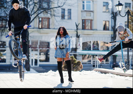 African american girl in jeans dress and two street boys jump on bmx bike and scooter. - Stock Photo