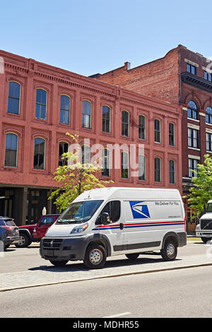 New modern U.S. Postal Service delivery van or mail truck parked on a city street making deliveries in downtown Montgomery Alabama, USA. - Stock Photo
