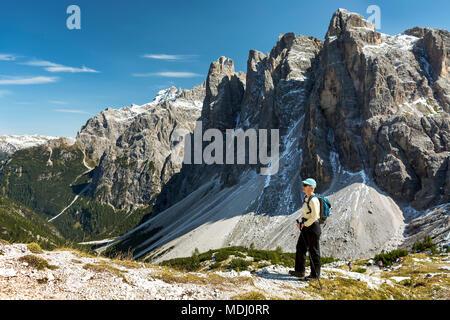 Female hiker overlooking valley against rugged mountain range and blue sky; Sesto, Bolzano, Italy - Stock Photo
