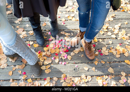 Footwear and legs of three women standing on a boardwalk in autumn; New Westminster, British Columbia, Canada - Stock Photo