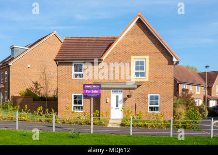 Purple bricks house for sale sign in front of a new house UK - Stock Photo