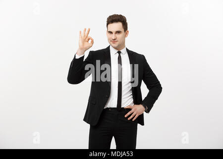 Business Concept: A handsome man in smart suit isolated on gray background showing ok sign. - Stock Photo