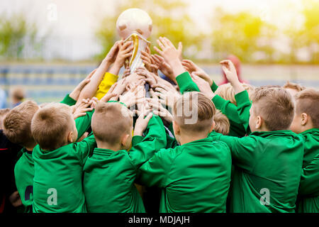 Kids Celebrating Soccer Victory. Young Football Players Holding Trophy. Boys Celebrating Sports Championship. Winning Team of Sport Tournament for Kid - Stock Photo