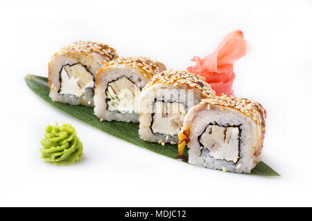 Exquisite and original rolls of sushi with eel, omelette and Philadelphia cheese laid out on a banana leaf. Isolated. Sushi roll on a white background - Stock Photo