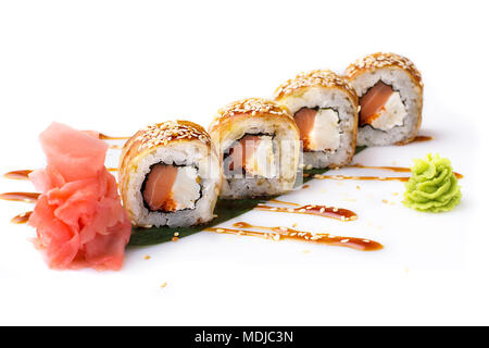 Appetizing and original sushi rolls with smoked salmon and Philadelphia cheese in an omelette laid out on a banana leaf. Isolated. Sushi roll on a whi - Stock Photo