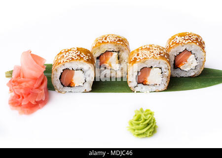 Exquisite and original sushi rolls with smoked salmon and cottage cheese in an omelette laid out on a banana leaf. Isolated. Sushi roll on a white bac - Stock Photo