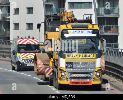 A Searle Group Volvo FH16 tractor unit towing a Nooteboom low-loader trailer carrying a W M Plant Hire Caterpillar CAT 345C long-reach excavator - Stock Photo