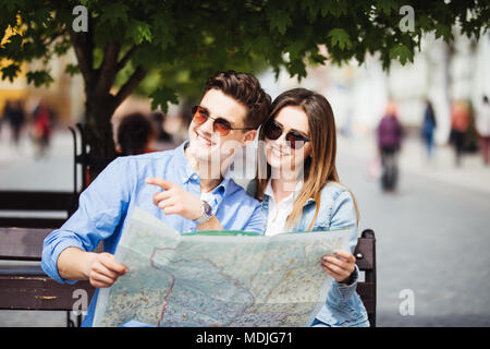 Couple of tourists searching location sitting on bench during a summer travel - Stock Photo