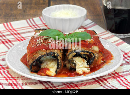 Two eggplant rolletini garnished with fresh basil leaves, a bowl of parmesan and a glass of red wine.  Macro front view. - Stock Photo