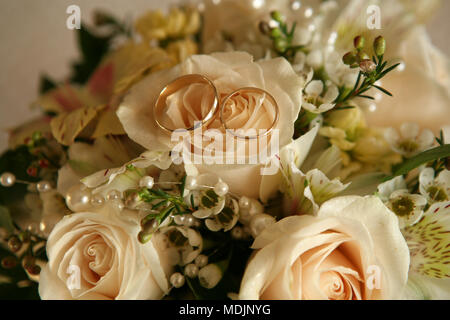 wedding bouquet with peach roses along with two wedding rings - Stock Photo