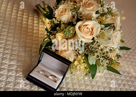 beautiful peach roses wedding bouquet sitting on a bed with the wedding rings in the box - Stock Photo