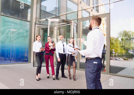 Meeting. Teamwork. The chief talks with the office staff against the background of a multi-storey office. A team of young employees are engaged in a d - Stock Photo