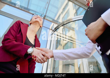 Handshake of two young girls against the background of a multi-storey office building. Make a deal. Friendly relations. Office staff. - Stock Photo