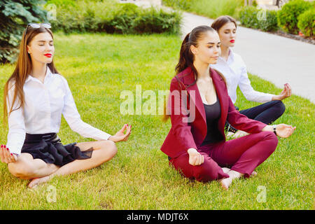office yoga three young girls in a lotus pose are sitting