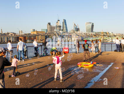 London, UK, 19th April, 2018. An entertainer on the south bank of the Embankment of the River Thames at Bankside blows bubbles to entertain children against a skyline background of iconic modern skyscraper buildings in the City of London. The sunny fine weather on the warmest April day in decades brought out good-natured crowds to enjoy the sunshine. Credit: Graham Prentice/Alamy Live News. - Stock Photo