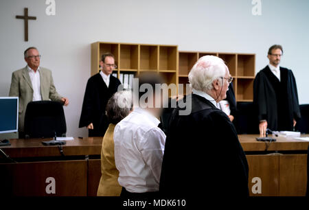 20 April 2018, Germany, Munich: A 38-year-old defendant (c) sits in court next to his lawyer Wilfried Eisell (r). He is charged with firing shots at a young female police officer at the train station of Unterfoehring near Munich in June of last year. Photo: Sven Hoppe/dpa - ATTENTION: individual(s) has/have been pixelated for legal reasons - Stock Photo
