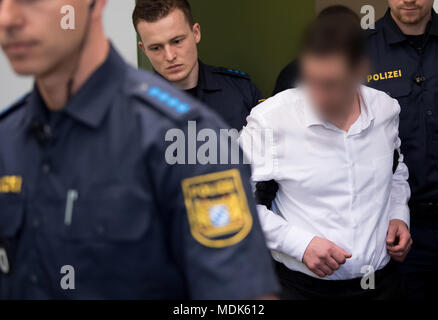 20 April 2018, Germany, Munich: A 38-year-old defendant (r) is escorted into court for his trial. He is charged with firing shots at a young female police officer at the train station of Unterfoehring near Munich in June of last year. Photo: Sven Hoppe/dpa - ATTENTION: individual(s) has/have been pixelated for legal reasons - Stock Photo