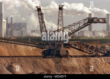 A lignite excavator is on 25.10.1998 in the lignite mining Garzweiler I. In the background, the power plant Niederaussem can be seen. The RWE Group remains unrestricted to the brown coal mining Garzweiler II. The discussion about an exit from nuclear energy has even strengthened the company in its attitude to use lignite as an energy source for electricity generation, said a RWE spokesman in Essen. He dismissed newspaper reports in which he had reported doubt about the economics of the large-scale project from within the company. Still the water legal approval stands out. | usage worldwide - Stock Photo
