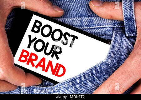 Handwriting text writing Boost Your Brand. Concept meaning improve your models name in your field overcome competitors written Mobile phone screen hol - Stock Photo