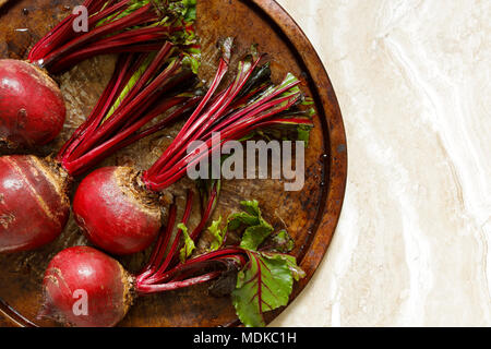 Fresh beetroots on metal tray on marble table with copy space right - Stock Photo
