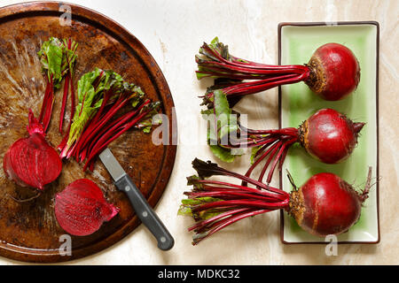 Fresh beetroots on green ceraminc tray and metal plate with knife on marble with copy space to right - Stock Photo