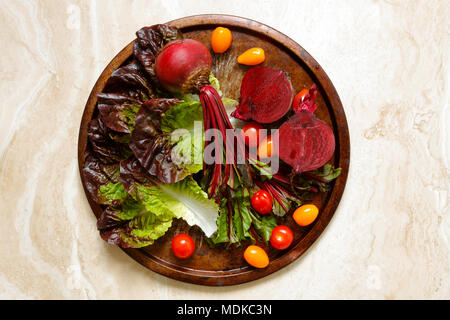 Fresh beetroots on metal tray with variety of cherry tomatoes and gem lettuce on marble table - Stock Photo