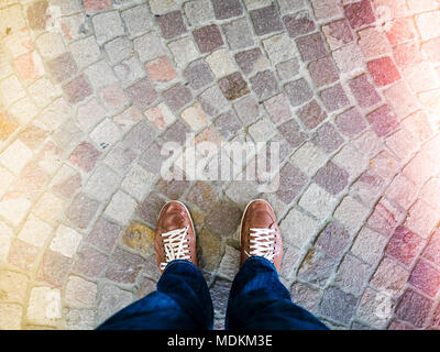top view of leather shoes on stone mosaic floor, colored light leaks coming from both sides, - Stock Photo
