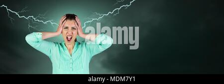 Lightning strikes and stressed woman with headache holding head - Stock Photo