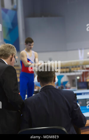 Young man gymnasts preparing in front of judge at the competition - Stock Photo