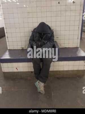 Man sleeps on bench in the 2nd Avenue subway station platform in Manhattan, NYC. - Stock Photo