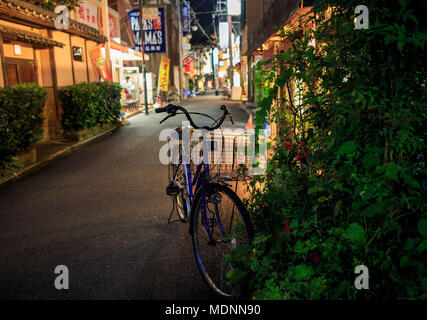 Osaka, Japan - September 2, 2013: A blue bicycle parked on the side of a small Japanese backstreet - Stock Photo