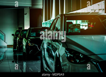Closeup new luxury compact car parked in modern showroom for sale. Car dealership office. Car retail shop. Electric car technology and business concep - Stock Photo