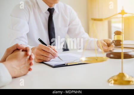 Justice and Law concept. Legal counsel presents to the client a signed contract with gavel and legal law or legal having team meeting at law firm in b