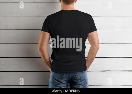 mockup of a black t shirt on a strong man holding your hands on your