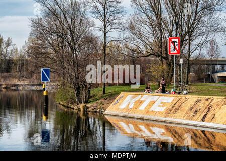 Berlin Charlottenburg-Wilmersdorf, Three young people picnic in park next to Schleusenkanal n Spring - Stock Photo