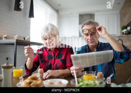 Portrait of senior marriage having morning breakfast together - Stock Photo