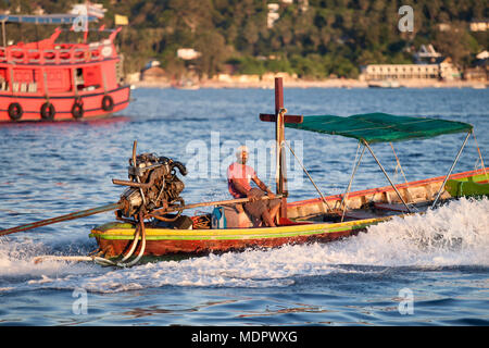 KOH TAO THAILAND - MARCH 5,2018 : long tail boat driver in koh tao vessel his vehicle passing had sai ree beach most popular traveling destination in  - Stock Photo