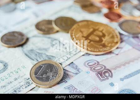 Bitcoin, euro, dollar and rubles coins on paper currency - Stock Photo