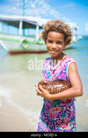 CAIRU, BRAZIL - CIRCA FEBRUARY 2018: Young girl selling souvenir shells from a small basket on the beach in Bahia. - Stock Photo