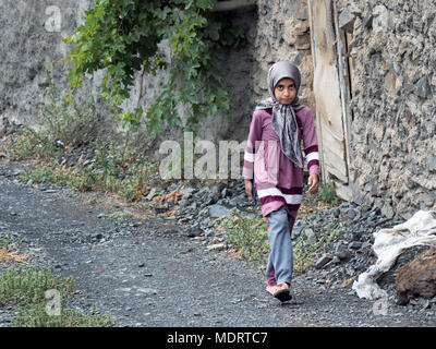 Muslim girl waling on a path in a rural village of northern Iran - Stock Photo
